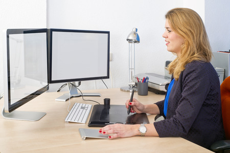 Young woman sitting behind a large desk and a dual screen computer, using a graphic tablet and track pad during design work