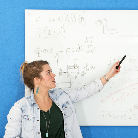 civil engineering: Young woman explaining a complex mathematical calculation in civil engineering she just wrote down on a white board Stock Photo