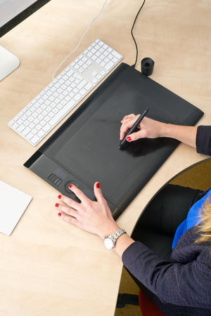 ergonomics: Woman with red finger nails working behind a grapic tablet, busy with computer aided design