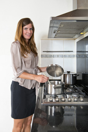 Young businesswoman cooking when she gets home after work. Life - work balance concept
