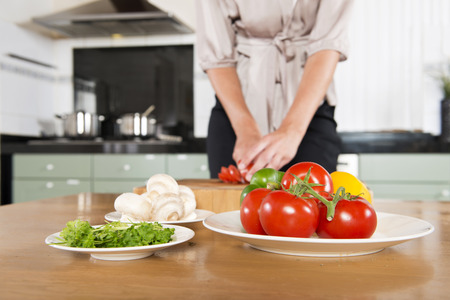 Fresh ingredients on various plates, being cut on a kitchen table, with a stove, pots and pans out of focus in the distance. Focus on the tomatoes in front photo