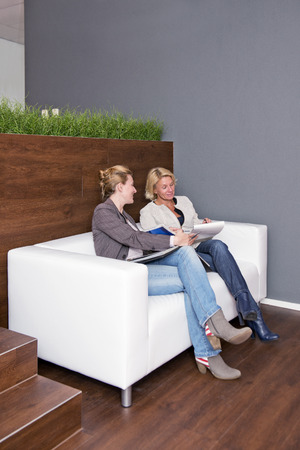 informal: Two businesswomen going over notes together during an informal business meeting on a couch
