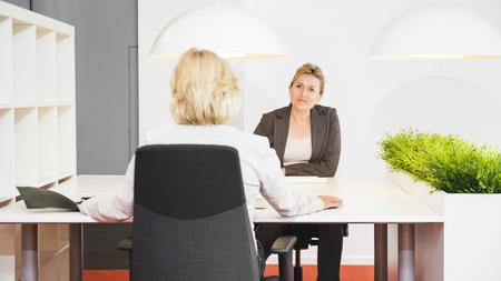 eachother: female entrepeneurs sitting opposite of eachother behind their desk, discussing the paperwork thats in front of them on the table Stock Photo