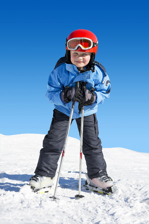 Young boy on skis, leaning on his poles, ready to hit the slopes photo
