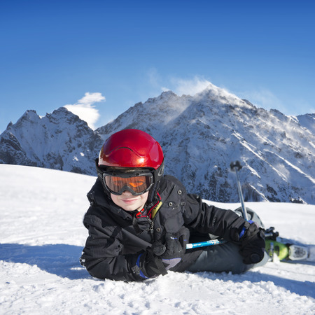 Young boy lying down in the snow, with his skis on, on a bright sunny day in the mountains,  photo