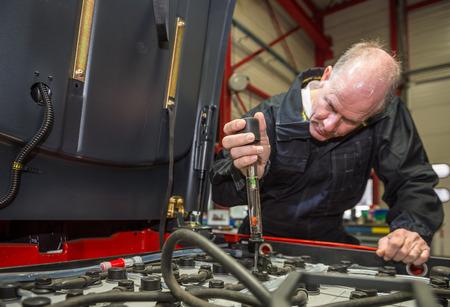 Mécanique est la mesure de l'acidité des batteries à partir d'un chariot élévateur
