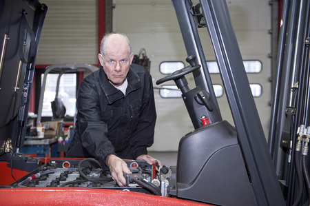 plugging: Senior mechanic hooking up the batteries of a forklift inside a garage and repair shop, wearing black overalls