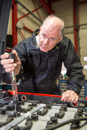 acidity: Mechanic is measuring the acidity of the batteries from a forklift