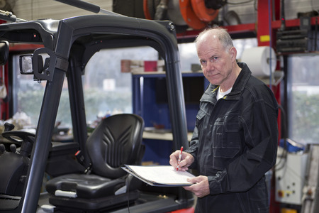 commissioned: Experienced Mechanic working through a checklist before a brand new forklift is delivered and commissioned in a workshop