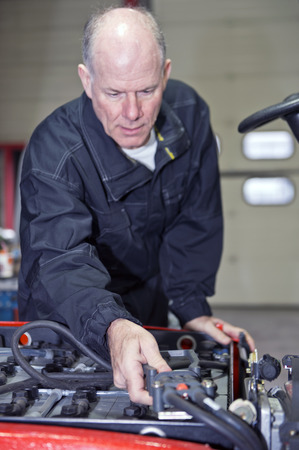hooking: Mechanic, hooking up the battery of a forklift to the electric engine in a workshop Stock Photo