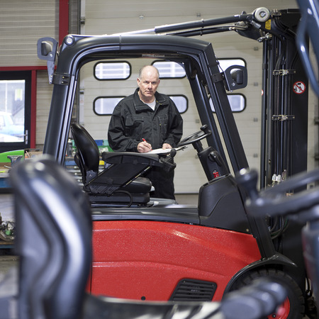 An experienced, and reliable, mechanic, with a clipboard and pen in his hand, working on a Forklift at a gearage, seen from the cabin of an adjacent forklift Stock Photo - 26406634