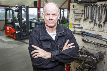 proud: Forklift mechanic stands confident in the garage with a wall of tools and the forklift in the background