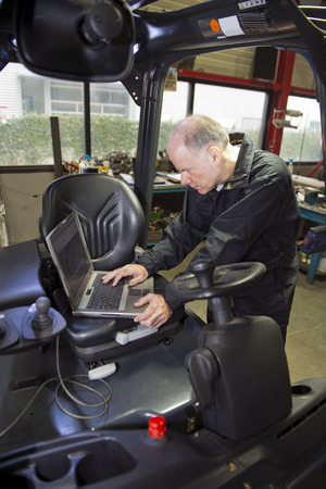 outputs: Mechanic checking the statistics of a forklift on a laptop, using its mechatronical interface. Mechatronic technology in internal transport