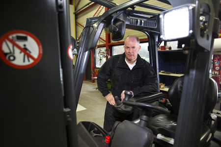 specialised: Experienced and specialised Mechanic, standing next to a forklift in a maintenance repair shop.