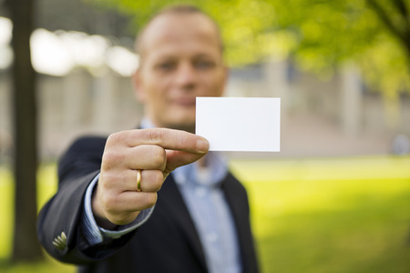courteous: Business man presenting a business card, standing outdoors on the grass in front of a convention center. Focus on the hand and business card