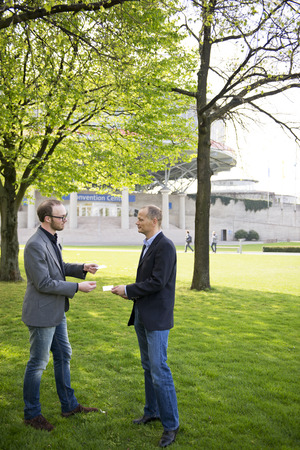 introductions: Two business men exchanging business cards at a convention center Stock Photo