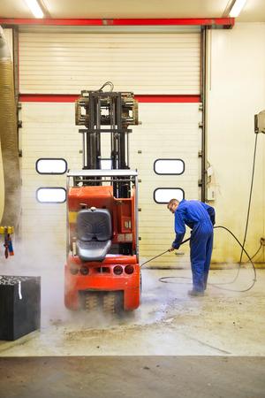 Travailleur, le nettoyage d'un chariot élévateur à l'envers, à l'aide d'un jet d'eau à haute pression dans un atelier de maintenance