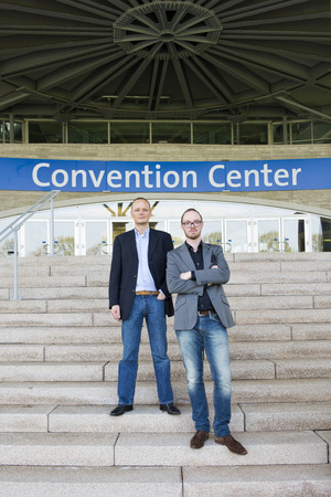 trade fair: Two attendees of a congress at a trade fair posing on the steps leading to the front entrance of the convention center.