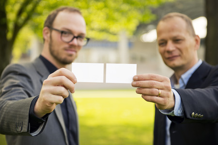 joining forces: Two smart casually dressed businessmen presenting their business cards to a new network
