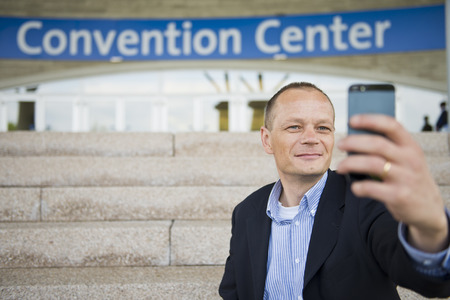 Business man taking a selfie with his smart phone in front of a convention center photo
