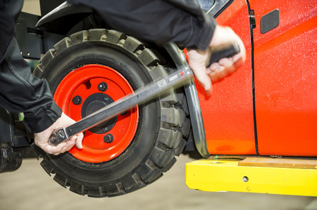 Maintenace on a forklift, a worker is changing the tyres   Stock Photo