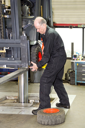 mot: Forklift mechanic replacing a front tyre on a forklift in a workshop