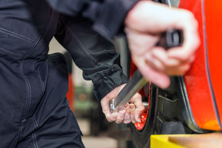 torque wrench: Man is changing the tyre of a forklift in the maintenance area