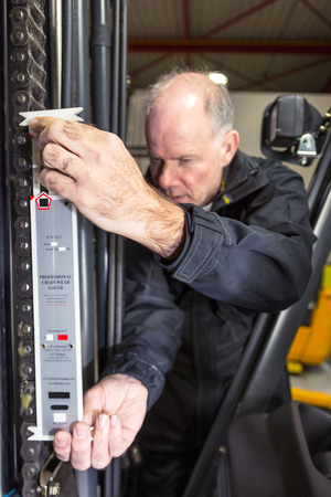 Man measuring the chain of a forklift photo