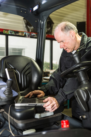 plc: A man working on forklift, filling in some date of the forklift  Stock Photo