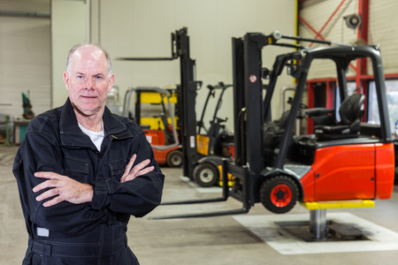 forklifts: man standing in front of a few forklifts in a maintenance service area  Stock Photo