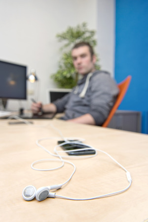 paperless: Ear phones, lying on a clean, paperless desk, with a man, working behind a computer . A connectivity concept Stock Photo