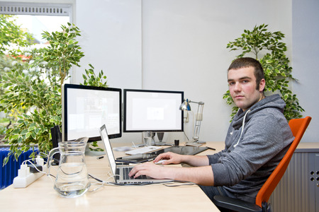 collaborating: Working in the cloud concept, with a young employee, using various electronic devices online, collaborating internationally through the cloud. The ideal of a paperless office concept Stock Photo