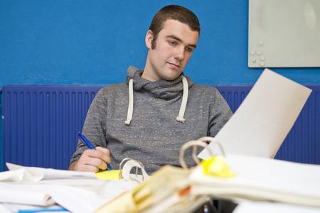 messy desk: Intern joven que trabaja en un escritorio desordenado, atestado de carpetas, documentos y tr�mites