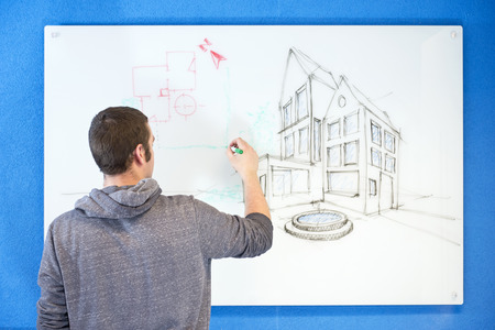 glassboard: Young architect, drawing ideas, plans and concepts in an isometric perspective on a white board