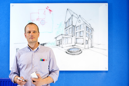 glassboard: Architect, holding a white board marker, standing in front of a design sketch of a residential structure on the glass board behind him