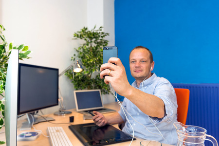 paperless: A business man taking a selfie in his clean and paperless office. Stock Photo