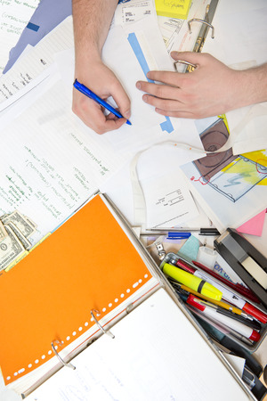 Messy desk, filled with documents, notes, pens and all sorts of office supplies, including a few dollar bills, with a hand taking notes on the back side of an enveloppe, seen from above. photo