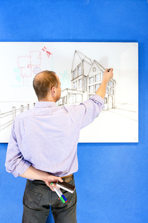 glassboard: Sketch artists standing in front of a whiteboard, drawing a concept of an architectural design of a residential structiure