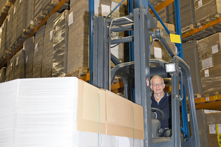 plano: Forklift driver in a forklift, carrying a large stack of flattened cardboard boxes