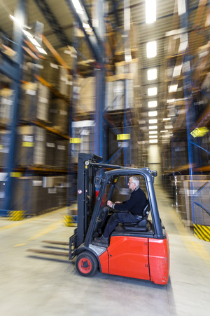 stockroom: A man driving a forklift trough a warehouse