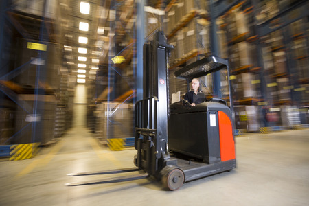 Panning shot of a reach truck forklift driving by in a warehouse.