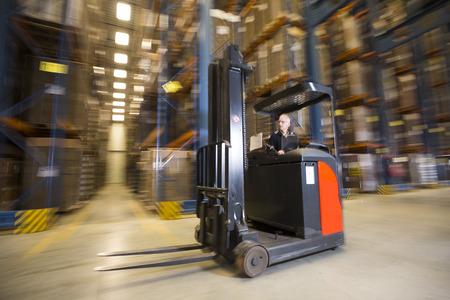 panning shot: Panning tiro di un carrello retrattile carrello elevatore di guida da parte in un magazzino.