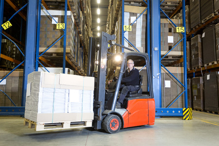plano: Forklift driver posing in front of a row with storage racks. On his fork he is transporting a pallet full of flat cardboard boxes.  Stock Photo