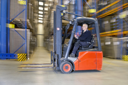 Panned image Forklift driving through a warehouse. Concept for internal logistics, just in time delivery, next day delivery, service industries and supply chain management. Panned image with slight motion blur. photo