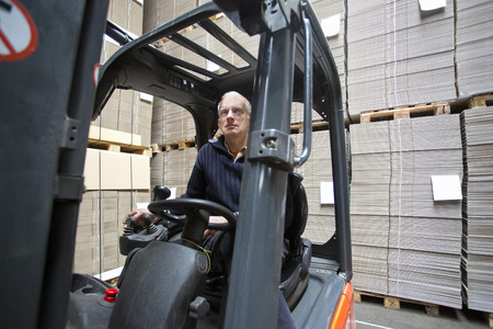 Forklift driver inside a forklift, manipulating a joystick in a warehouse full of pallets empty, plano, cardboard boxes photo