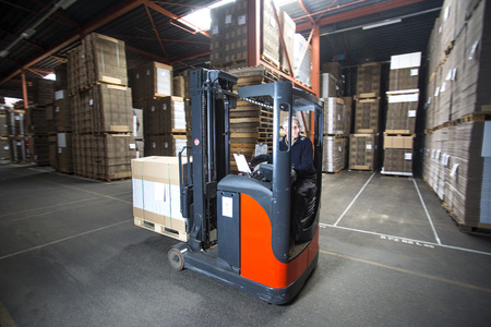 distributing: Reach truck is piling up pallets in a low section of the warehouse