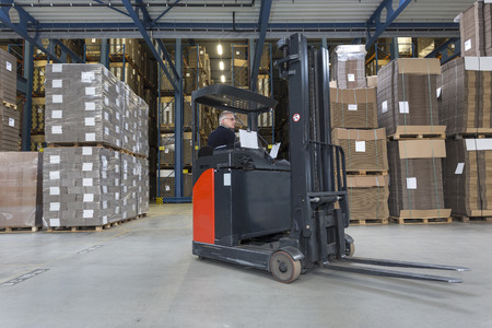reach truck: Reach truck driving around cardboard boxes in a warehouse.  Stock Photo