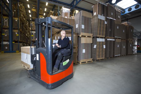 distributing: Reach truck driving around the corner in a warehouse where cartboard boxes are stored.