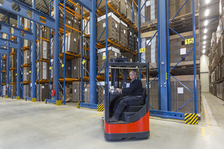 experienced operator: Man driving his reachtruck into a row with storage racks. In the storage racks there are cardboard boxes stored.  Stock Photo