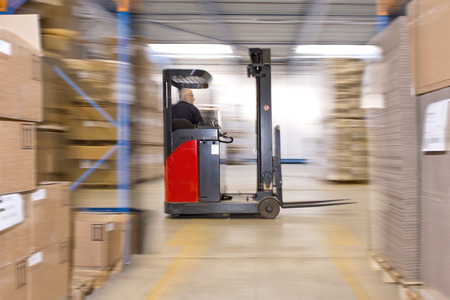 Reach truck forklift driving past an isle in a warehouse at speed. A panned image, with stock and cardboard boxes in the shelfs of the storage racks. Conceptual image about internal logistics, shipping and delivery, distribution and handling of various su Stock Photo